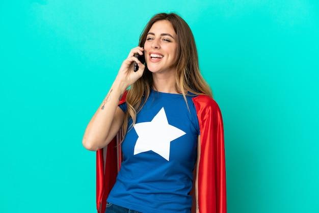 휴대 전화와 대화를 유지하는 파란색 배경에 고립 된 슈퍼 영웅 백인 여자