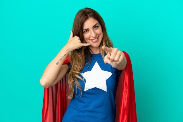 電話のジェスチャーをし、正面を指す青い背景に分離されたスーパーヒーロー白人女性