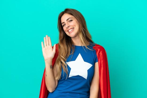 Кавказская женщина супергероя изолирована на синем фоне, салютуя рукой с счастливым выражением лица