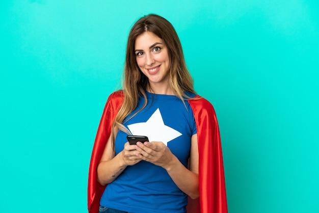 모바일로 메시지를 보내는 파란색 배경에 고립 된 슈퍼 영웅 백인 여자