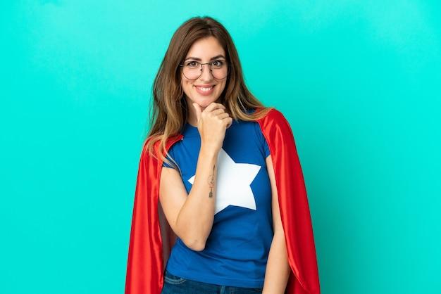 안경과 웃는 파란색 배경에 고립 된 슈퍼 영웅 백인 여자