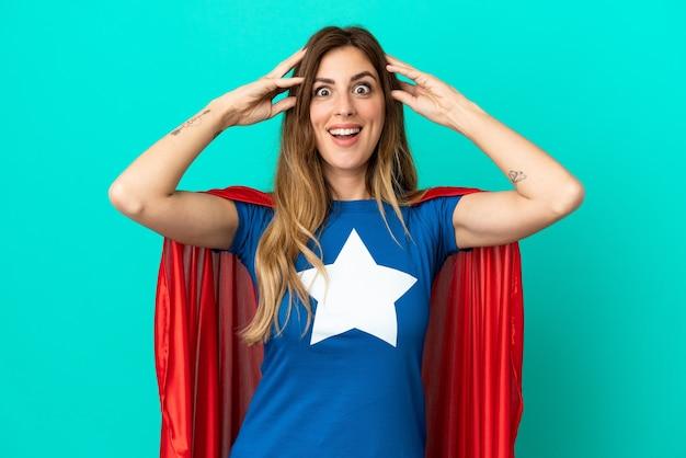 Кавказская женщина супергероя изолирована на синем фоне с выражением удивления