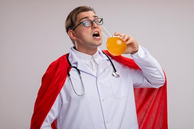赤いマントに白衣を着て、首に聴診器を持ったグラスを身に着けているスーパーヒーロードクターの男が白い壁の上に立ってそれを飲むつもりの黄色い液体のフラスコを持っています