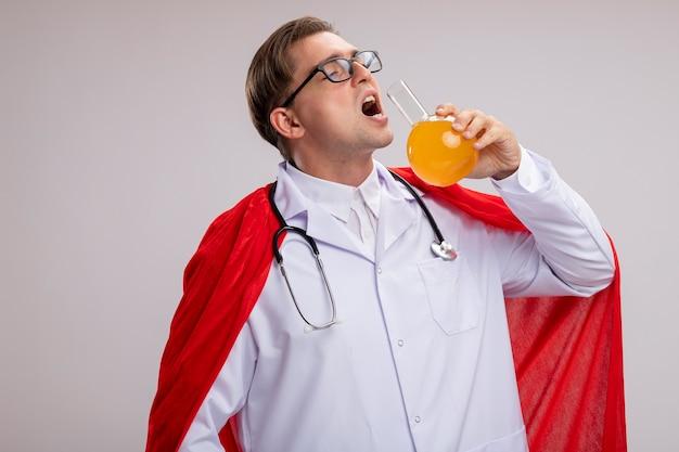 赤いマントに白衣を着て、首に聴診器を持ったグラスを身に着けているスーパーヒーロードクターの男が白い壁の上に立って黄色い液体を飲みに行くフラスコを保持しています