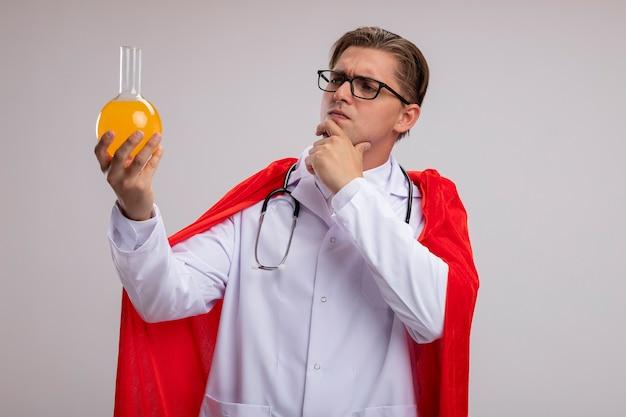 赤いマントの白衣と首の周りに聴診器を持った眼鏡をかけたスーパーヒーローの医者の男が白い壁の上に立って困惑している黄色い液体のフラスコを持っています