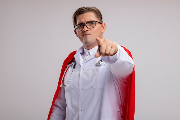 Super eroe medico uomo indossa camice bianco in mantello rosso e occhiali con lo stetoscopio intorno al collo che punta con il dito indice sorridente in piedi sopra il muro bianco