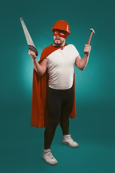 Super hero handyman holding saw and hammer. man wearing red helmet, mask and cape holds building equipment standing on biscay green background. handyman concept