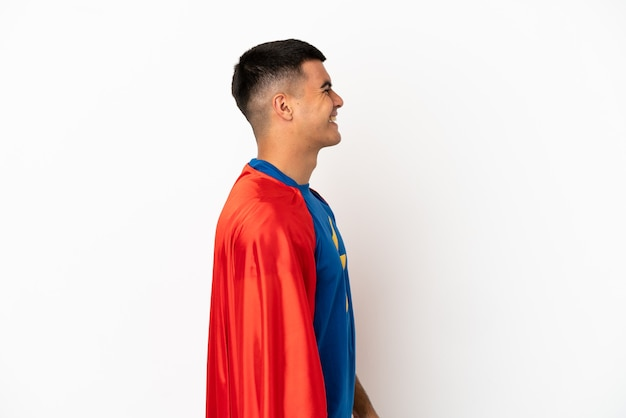 Super hero over isolated white background laughing in lateral position