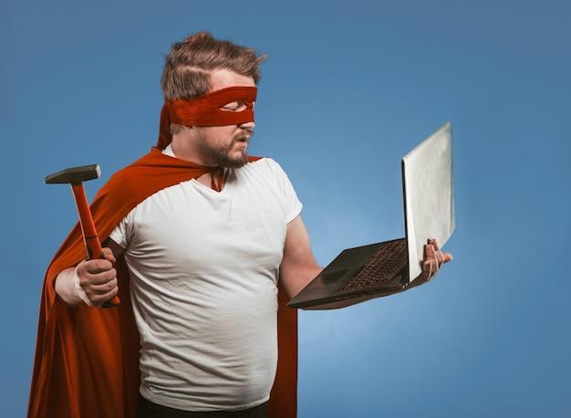 スーパーヒーローの男がハンマーでラップトップコンピューターを粉砕または修復しようとしています。