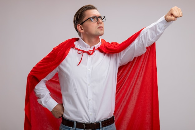 Uomo super eroe in mantello rosso e occhiali che osserva da parte con la faccia seria che fa il gesto vincente con la mano pronta ad aiutare in piedi sul muro bianco