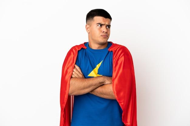 Супергерой на изолированном белом фоне, делая жест сомнения, поднимая плечи