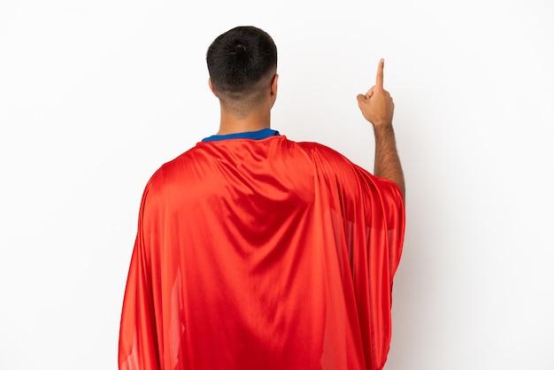 Супергерой на изолированном белом фоне, указывая указательным пальцем назад