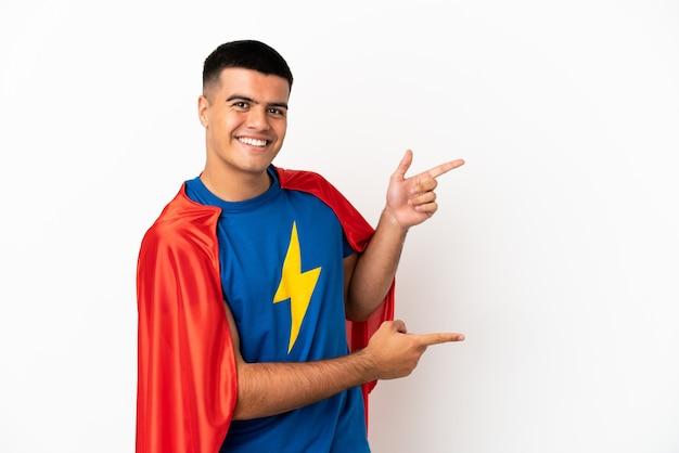 Супергерой на изолированном белом фоне, указывая пальцем в сторону и представляя продукт