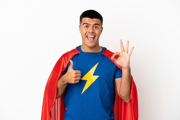 孤立した白い背景の上のスーパーヒーローは、okサインと親指を立てるジェスチャーを示しています