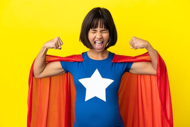 Супергерой беременная женщина, изолированные на желтом фоне, делает сильный жест
