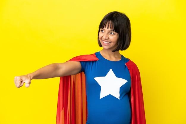 제스처를 엄지손가락을 포기 하는 노란색 배경에 고립 된 슈퍼 영웅 임산부