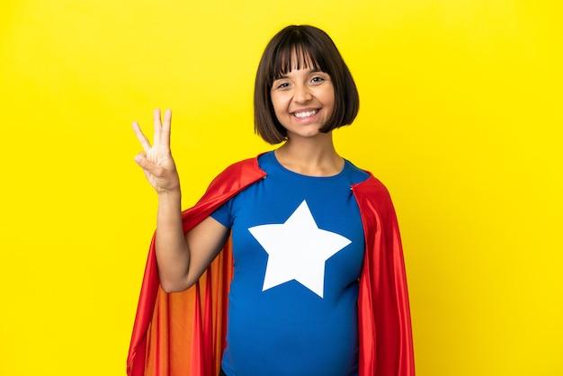 幸せな黄色の背景に分離されたスーパーヒーローの妊娠中の女性と指で3を数える