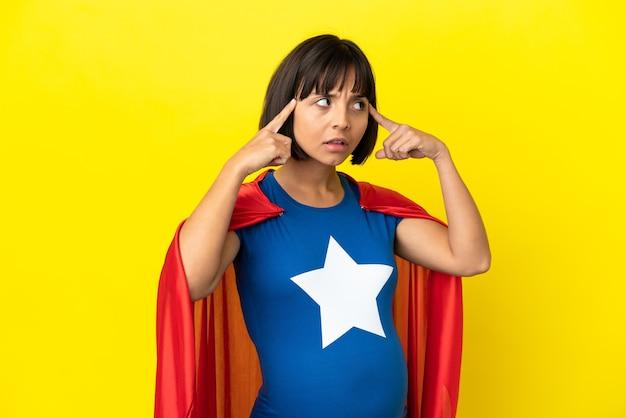 疑問と思考を持って黄色の背景に分離されたスーパーヒーロー妊婦