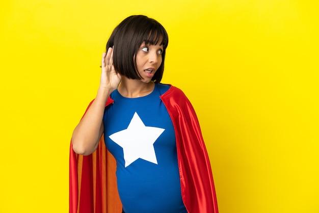 Супергерой беременная женщина изолирована на желтом фоне, слушая что-то, положив руку на ухо