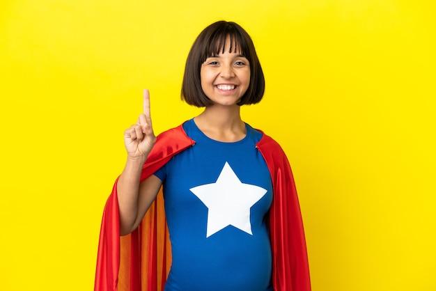 素晴らしいアイデアを指している黄色の背景に分離されたスーパーヒーロー妊婦
