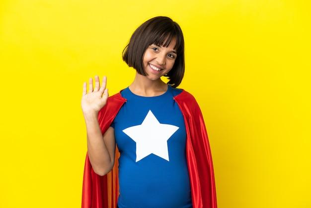 Супергерой беременная женщина изолирована на желтом фоне, салютуя рукой с счастливым выражением лица