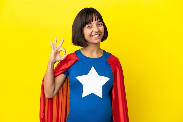 指でokサインを示す黄色の背景に分離されたスーパーヒーロー妊婦
