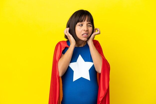 Супергерой беременная женщина изолирована на желтой стене разочарована и закрывает уши