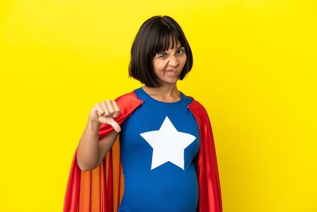 부정적인 표현으로 아래로 엄지 손가락을 보여주는 노란색 벽에 고립 된 슈퍼 영웅 임신 한 여자