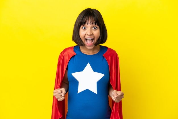 Super hero pregnant woman isolated on yellow background celebrating a victory in winner position