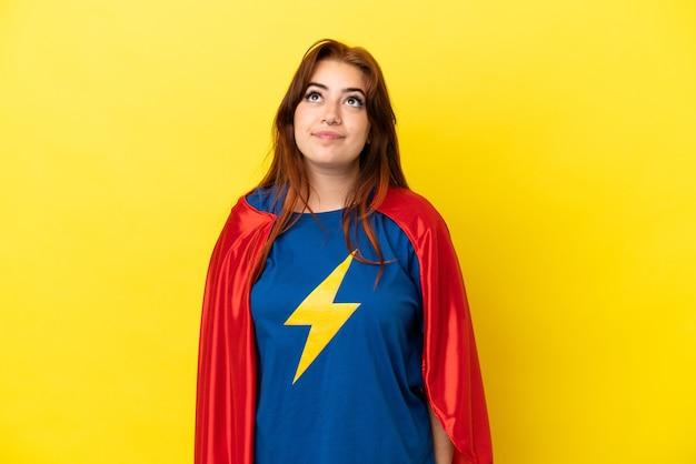 Рыжая женщина супергероя изолирована на желтом фоне и смотрит вверх