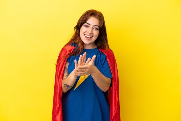 Рыжая женщина супергероя изолирована на желтом фоне аплодирует после презентации на конференции