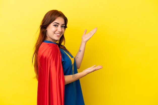 来るように誘うために手を横に伸ばして黄色の背景に分離されたスーパーヒーロー赤毛の女性