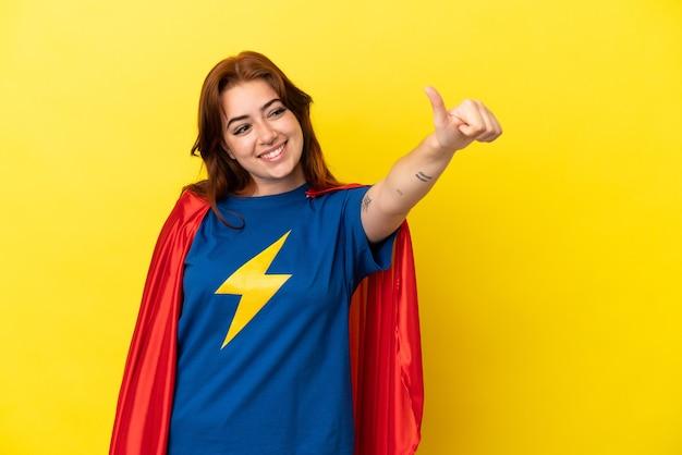 노란색 배경에 고립 된 슈퍼 영웅 빨간 머리 여자는 제스처를 엄지손가락을 포기