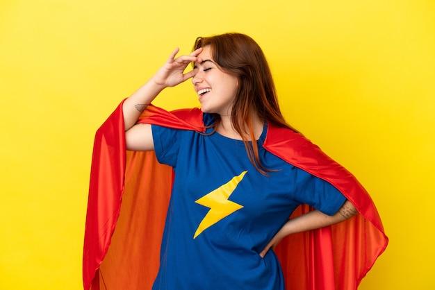 Рыжая супергеройская женщина, изолированная на желтом фоне, что-то поняла и намеревается решить