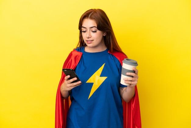 Рыжая женщина супергероя изолирована на желтом фоне, держа кофе на вынос и мобильный