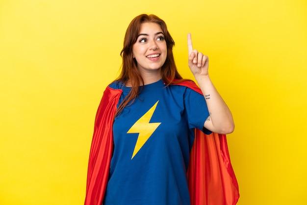 Рыжая супергеройская женщина изолирована на желтом фоне, намереваясь реализовать решение, подняв палец вверх