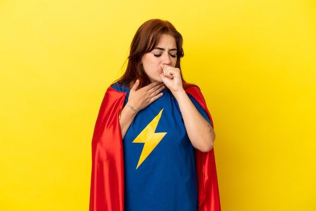 노란색 배경에 격리된 슈퍼 히어로 빨간 머리 여성은 기침을 하고 기분이 나쁩니다