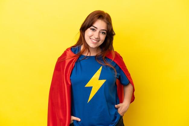Рыжая женщина супергероя изолирована на желтом фоне смеясь