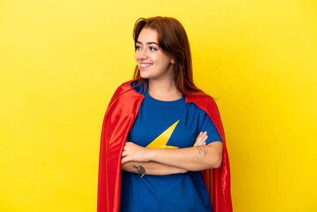 Рыжая женщина супергероя изолирована на желтом фоне, глядя в сторону