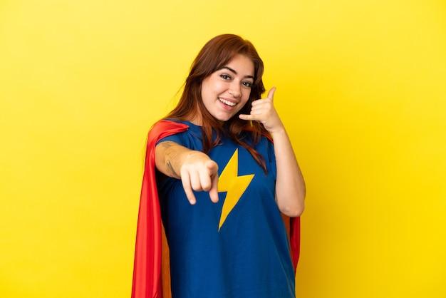 Рыжая женщина супергероя изолирована на желтом фоне, делая жест по телефону и указывая вперед