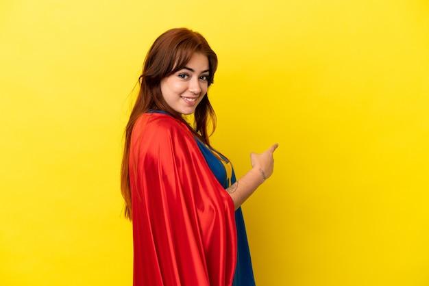 Рыжая женщина супергероя изолирована на желтом фоне, указывая назад