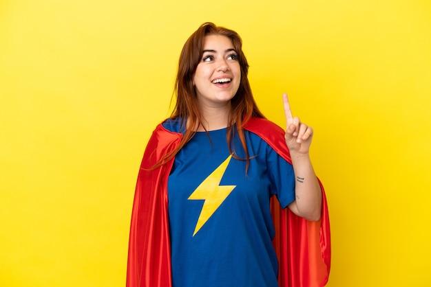 Рыжая женщина супергероя изолирована на желтом фоне, указывая вверх и удивлена