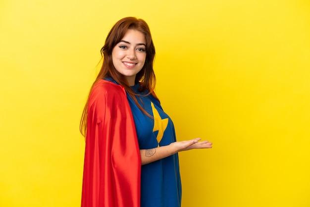 Рыжая женщина супергероя изолирована на желтом фоне, представляя идею, улыбаясь в сторону