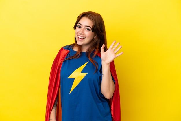 幸せな表情で手で敬礼黄色の背景に分離されたスーパーヒーロー赤毛の女性