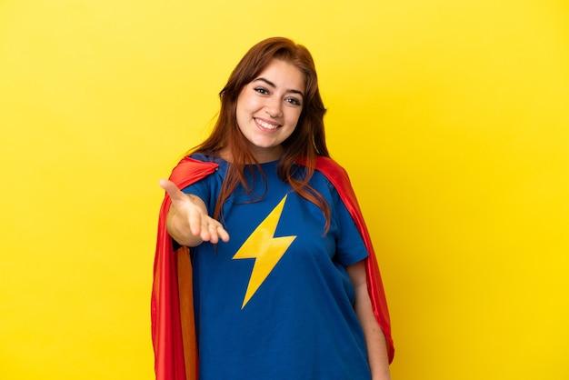 노란 배경에 격리된 슈퍼 히어로 빨간 머리 여성이 좋은 거래를 성사시키기 위해 악수를 하고 있다