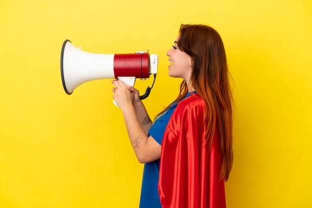 Рыжая женщина супергероя изолирована на желтом фоне и кричит в мегафон