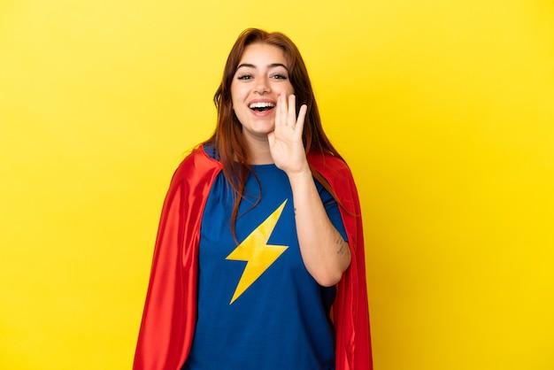 Рыжая женщина супергероя изолирована на желтом фоне и кричит с широко открытым ртом