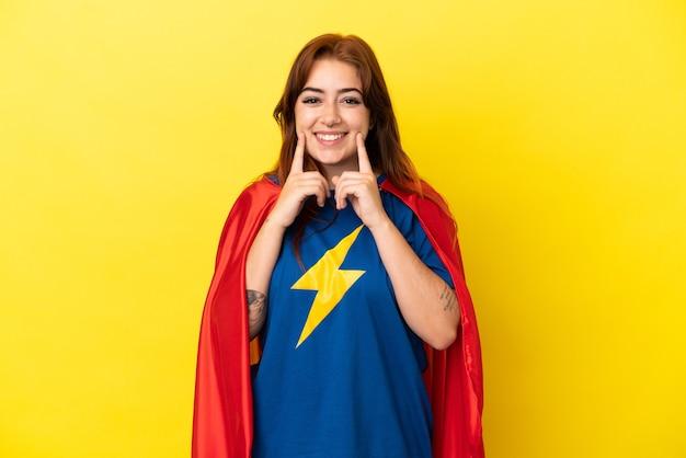 Рыжая женщина супергероя изолирована на желтом фоне, улыбаясь счастливым и приятным выражением лица