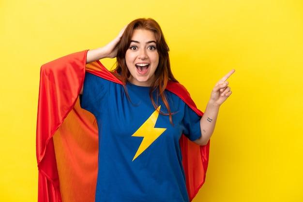 Рыжая женщина супергероя изолирована на желтом фоне удивлена и показывает пальцем в сторону