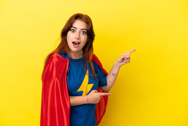 Рыжая женщина супергероя изолирована на желтом фоне удивлена и указывает сторону